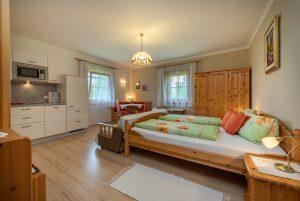 Bild: Lacknerhof Ferienwohnung Bergpanorama: Blick zur Küchenzeile und zum Doppelbett