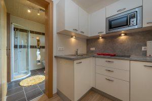 Bild: Lacknerhof Ferienwohnung Bergpanorama: Blick zur Küchenzeile und ins Badezimmer