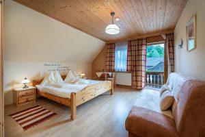 Bild: Lacknerhof Ferienwohnung Glantal: Schlafzimmer, Am Bild: Doppelbett, gemütliche Couch, Blick zum Balkon hinaus;