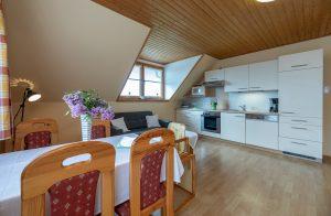 Bild: Lacknerhof Ferienwohnung Glantal: großzügiger Wohnbereich, Blick von der Essgarnitur zur Küchenzeile und gemütlicher Couch