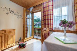 Bild: Lacknerhof Ferienwohnung Glantal: Schlafzimmer, Am Bild: Blick zum Balkon hinaus, davor die Essgarnitur und Spielzeug für Kinder